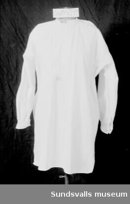 Vit skjorta med vid ärm som rynkats ihop vid manschetten, vilken knäpps med en silverfärgad knapp. Rund hals med smal kragkant. Påsytt smalt bröststycke med dold knäppning. Mörkrosa broderat monogram mitt fram.