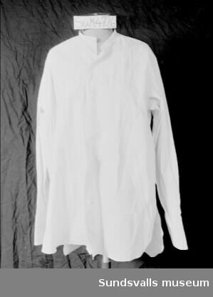 Skjorta i vitt bomullstyg med ståkrage att fästa löskrage på. Knäppning mitt fram med sex vita knappar. Lång ärm med dubbelvikta manschetter med plats för lösa manschettknappar. Sprund på var ärm som knäpps med en vit plastknapp. Sprund i båda sidosömmarna. Skjortan är märkt 'STENSTRÖMS SKJORTOR', fabrikat.