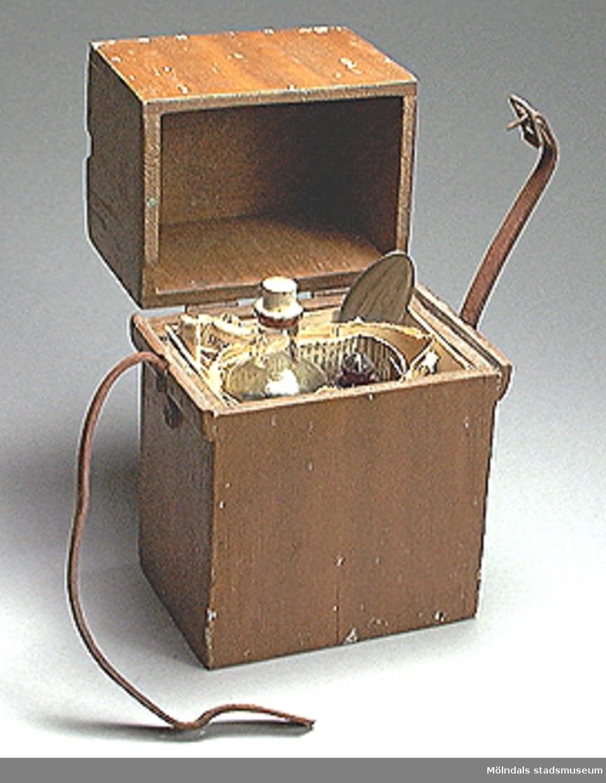 Egentillverkad låda för medicin, innehåller tre flaskor för invertes bruk, från Dr. Malmström 13/6-1938. Flaskorna är inlindade i tidningar från Göteborgs Handels och Sjöfartstidning från 2/4-1938. I lådan finns en matsked i rostfritt stål för intaget av medicinen.Föremålen kommer i från Rote L 1 A, Frankegatan 2. Dödsboet har en god man som heter Gunnar Torén. Huset genomgår just nu en omfattande dokumentation från museet och Göteborgs universitets byggnads- antikvarielinje.