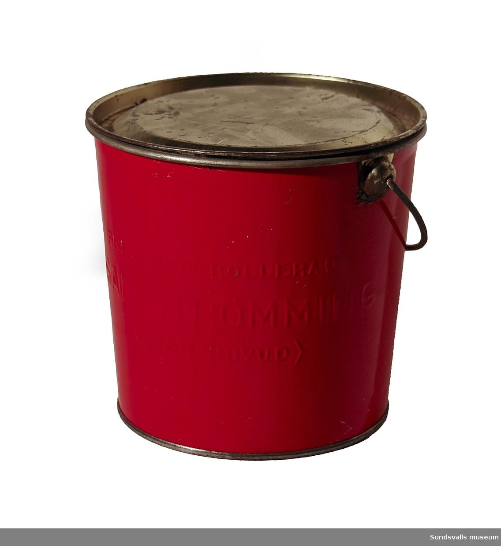 Hink för strömming med handtag och lock. Hinken är rödlackerad och bär texten 'PRIMA KONTROLLERAD SALTSTRÖMMING (UTAN HUVUD)'.