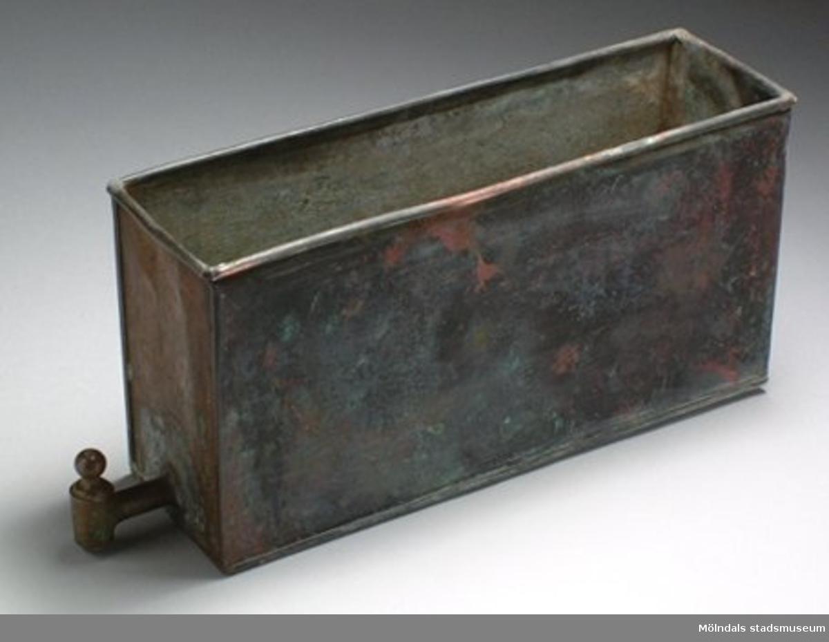 Behållaren satt invid gjutjärnspisen och uppvärmdes av denna. Den ingick i Mölndals museums 1930-talsinredning.