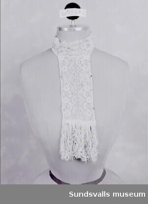 SuM 5169:1-5, isättningar tillverkade av tyll och bomull. SuM 5169:1 är 37,5 cm lång och knäppes runt halsen med tryckknappar. SuM 5169:2 är 34 cm lång, inklusive fransar och knäppes runt halsen med tryckknappar. SuM 5169:3 är 28 cm lång och sydd av vitt bomullstyg och dekorerad med spets och svarta band. Den fästs runt halsen och har en spetskantad krage. SuM 5169:4 är 18 cm lång och knäpps i ryggen med tryckknappar. Är även försedd med knytband av bomull. SuM 5169:5 är 22 cm lång och knäpps runt halsen med tryckknappar.