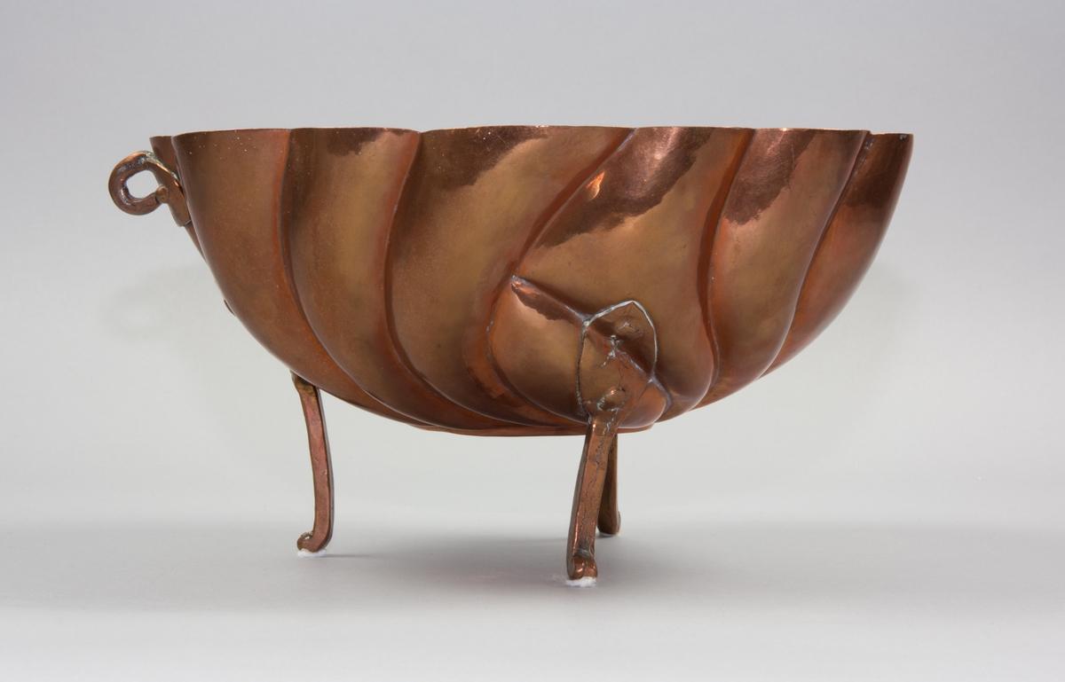 Puddingform av koppar. Tre fötter nitade mot formen. Ovalt utformad med ett böljande vridet mönster som utgår ifrån en centrerad oval medaljong. I kanten en nitad bricka med ögla. I öglan en ståltrådsögla för upphängning. Invändigt förtent.