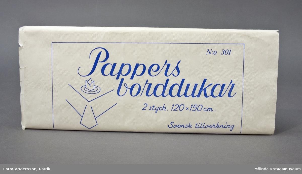 Bordsduk, gjord av vitt papper med präglat damastmönster. Två stycken dukar, vikta och sammanlagda, som slagits in i pappersark med samma mönster. Omslaget är förseglat med sigill (svan på vatten).