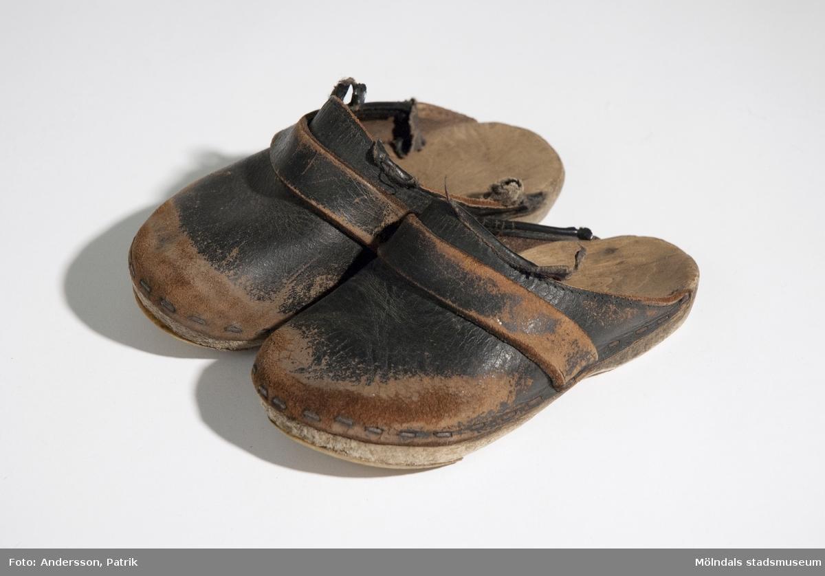 Ett par svarta trätofflor i barnstorlek från 1970-tal.Mycket slitna. Den vanligaste modellen av träsko i Sverige är den med sula i trä och ovandel av läder.