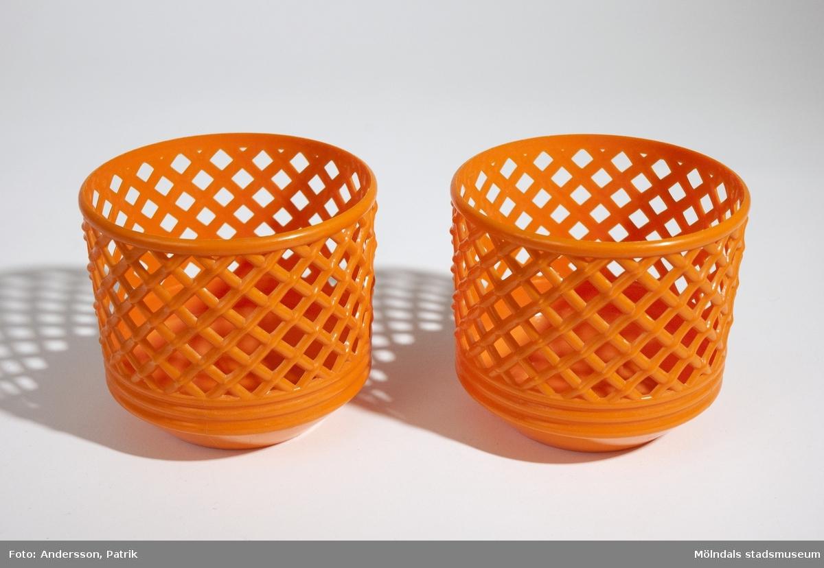 2 st blomkrukor. De är orange och har ett flätat/håligt mönster. Båda är lika stora.Mått på en blomkrukaHöjd: 100 mm, Diam: 110 mmGivaren Kerstin Olofsson använde dessa under 1970-talet.