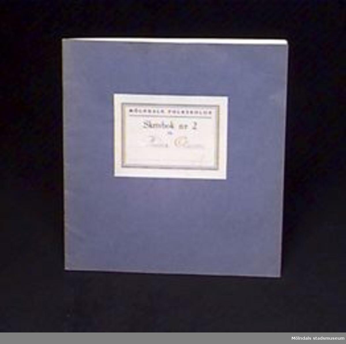 """Blå skrivbok med linjerade sidor. På omslaget en etikett med """"MÖLNDALS FOLKSKOLOR/Skrivbok n:r 2 för"""" samt skrivet med bläck: """"Rune Olsson"""" och ett """"A"""" skrivet med rödpenna. Givaren gick hela sin skoltid i Toltorpsskolan."""