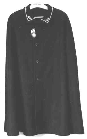 Regnkrage med guldgalon och två krönta posthornsemblem på den nedvikta kragen. En knapprad med fyra svarta knappar. Regnkragensaknar ärmar, foder och fickor. Tillverkad av impregnerat, starkt och lätt, mörkblått ylletyg och tillverkas beträffande halsvidden i tre olika storlekar. På ett vidhängade sigill från Postverkets allmännapersedelförråd står att regnkragen är inköpt från Firma K.W.Lundberg, Stockholm.