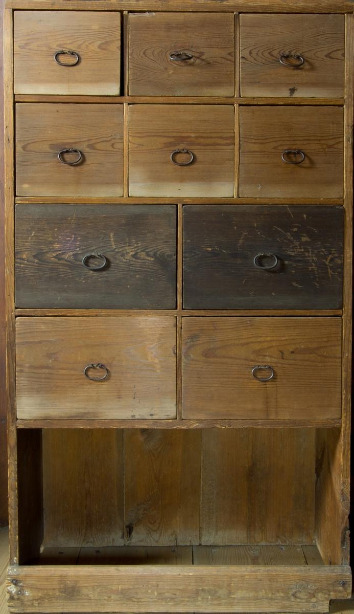 Kryddskåp i furu. Tio lådor i fyra lådplan, olika format, samtliga med draghandtag i järn. Nertill fotställning med tvärslå framtill.