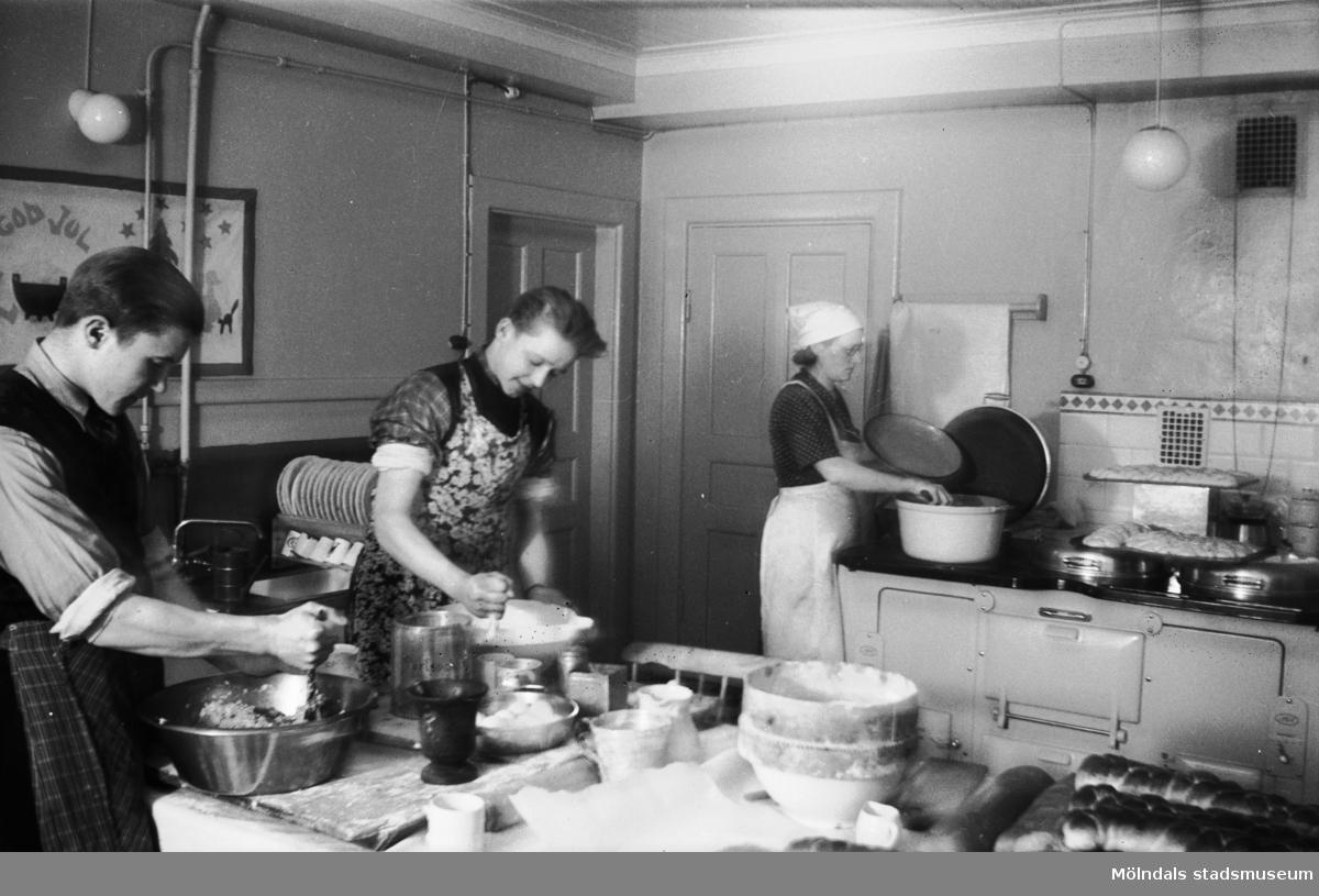 """Mölndals barnhem (f.d. Holtermanska) Rudbergsgatan. Tre personer som lagar mat. Direktören Martin Holterman i Ostindiska kompaniet ägde Åby gård. 1782 skänkte han 3000 daler silvermynt till Fässbergs församling + ett nybyggt skolhus och trädgård på gårdens ägor vid Åby by. I skolan skulle 10 fattiga barn undervisas i """"kristendom, skrivande och något räknande. Holtermans skola fanns kvar till 1875. Då hade donationens ändamål ändrats, och man byggde i stället ett barnhem kombinerat med småskola. 1914 brann barnhemmet och 1915 byggdes ett nytt barnhem på samma tomt. 1929 överlämnades barnhemmet till Mölndals stad."""
