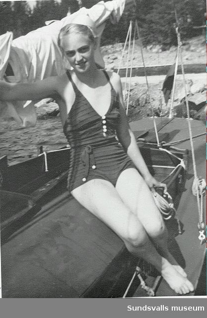 Kvinna i baddräkt sitter på en segelbåt.