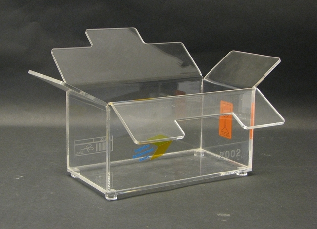 """Glaskonst i form av ett öppnat paket i plexiglas. På """"paketet"""" finns en orange """"fragile etikett"""" avbildad samt symbolen för Posten Logistics Award och en avsändarstreckkod med konstnärens namn """"Sylvia"""" angivet. Till paketet hör också två i plexiglas formade knoppförsedda kvistar. Konstverket har utgjort ett pris som Posten Logistik AB utdelat under rubriken: Posten Logistics Award. Priset tilldelades 2002 företaget Bergman & Beving med följande motivering: Bergman & Beving har genom ett långsiktigt logistikarbete och sin e-handelsportal """"Toolstore"""", på ett kreativt sätt förenklat hela försörjningskedjan - från tillverkare och grossister till återförsäljare och slutkunder. Bergman & Beving har genom Toolstore tagit ett större grepp över värdekedjan genom effektivare försörjning till sina befintliga kunder och återförsäljare, samtidigt som man har skapat en plattform för framtida expansion till nya marknader."""