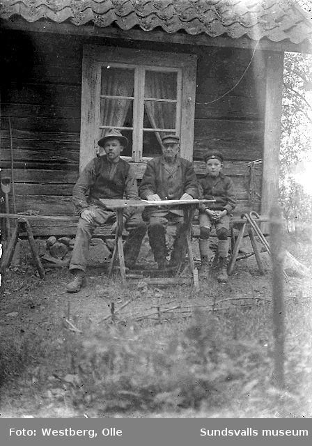Två män och en pojke vid trädgårdsbord utanför ett bostadshus.