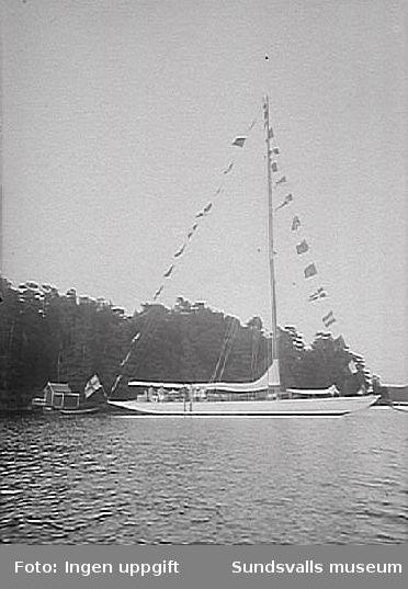 """Segelbåten """"Allona"""" med beslagna segel och stor flaggning/flaggning över topp, och en jolle förtöjd i aktern. Vid strandkanten finns ett badhus.""""Allona"""" beställdes av Wilhelm Bünsow, med Lennart Norström som senare ägare. Hon byggdes 1899 på Stockholms Båtbyggeriaktiebolag, troligen ägt av August Plym. Konstruktören var ingenjör Axel Nygren.Längd över allt, l ö a, var 26 meter, längd efter vattenlinjen, l v l, 19 meter, bredd 5,20 meter, djupgående 3,70 meter. Deplacementet var på 9 ton. Segelarean omfattade 300 m2 (375 m2 ursprungligen, före omriggning). Båten var utrustad med gaffelrigg, bermudasrigg, mesanmast (för att sätta segelmängden lättare?). I kajutan fanns sex kojer, i chefshytten och i styrmanshytten vardera fyra kojer, samt tre kojer i skansen."""
