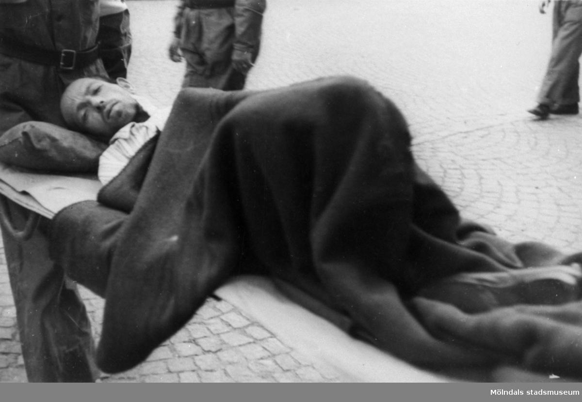 """""""Karantänsförläggning"""" på Kvarnbyskolan för flyktingar från koncentrationsläger i Tyskland 1945. En manlig flykting buren på bår av Röda Korsets personal."""
