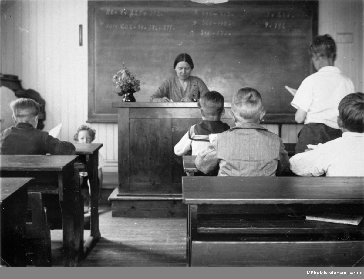 """Valdeborg Johansson med sina elever i klassrummet, våren 1934. Text på fotots baksida: """"När vi sitta i vår bänk"""". Samma elever som på bild 1992_0006, 0007. Ur Valdeborg Johanssons fotoalbum."""