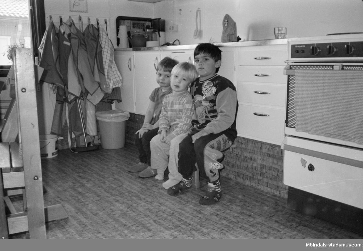 Tre barn som sitter på en liten pall framför en diskbänk. De tittar mot fotografen. Katrinebergs daghem, 1992-93.