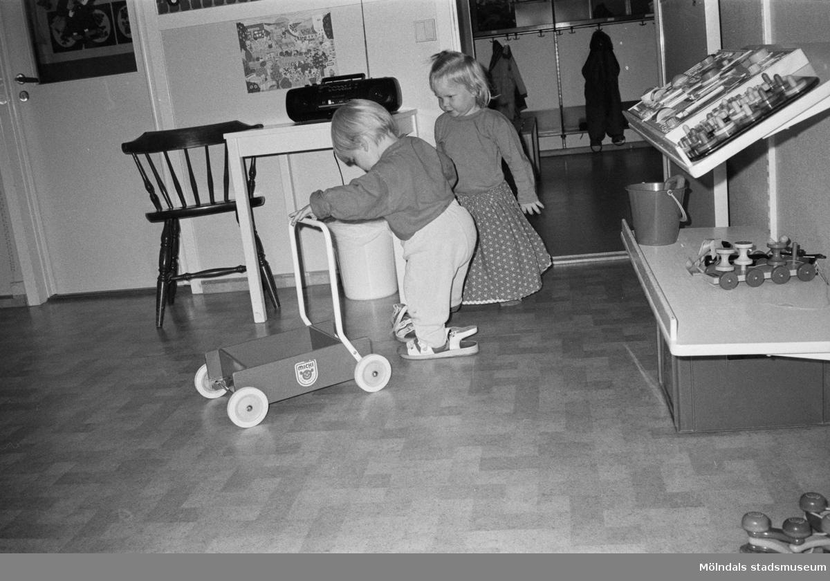 """Två barn leker med en """"Lära-gå-vagn"""". Det ena barnet provar ett par vita vuxen-sandaler. Vid sidan av dem finns vägghyllor med leksaker. Lille Skutt, Katrinebergs daghem, 1992."""