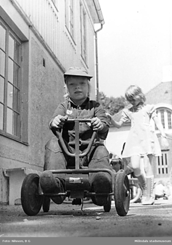 En pojke leker med trampbil på gårdsplanen utanför huset. I bakgrunden går en flicka. Holtermanska daghemmet juni 1973.