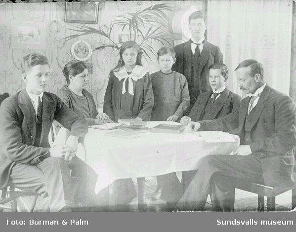 Familjeporträtt kring bord.