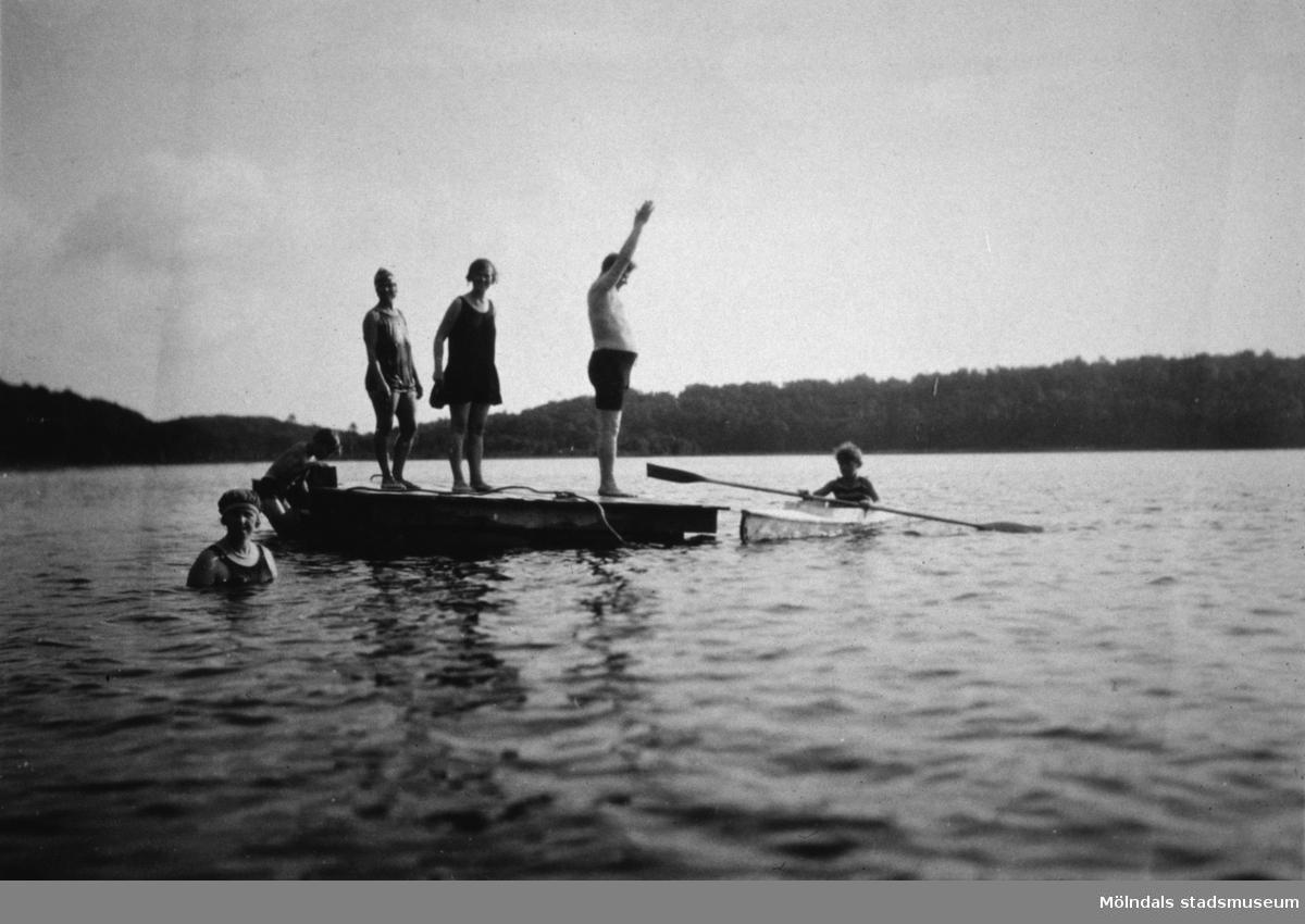 Män och kvinnor på en flotte samt en person i en kajak. Ev. vid Tulebosjön.