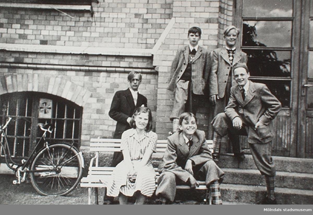 Fem pojkar och en flicka sitter eller står framför stora skolan på Stretereds skolhem. Okända personer och årtal.