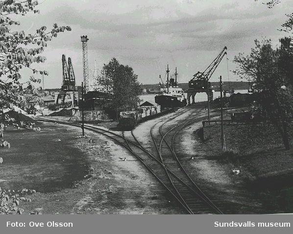 """Text: """"Del av hamnen, järnvägsgropen, med Alnö i fonden, sedd från järnvägsbron""""."""
