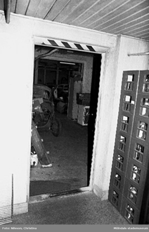 Interiör i fabriksbyggnad. Olika fordon i rummet innanför.
