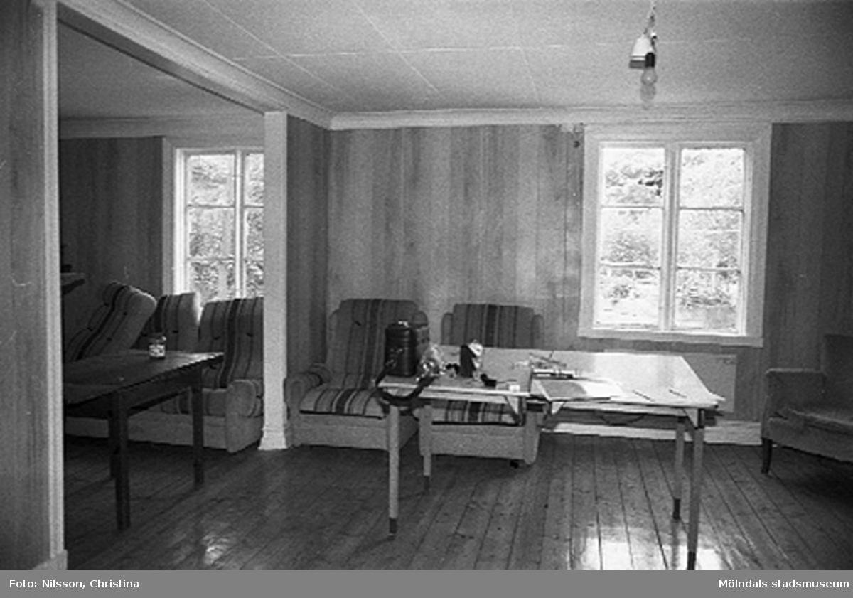 Interiör i fabriksbyggnad: två möblerade rum, avdelat med ett valv.