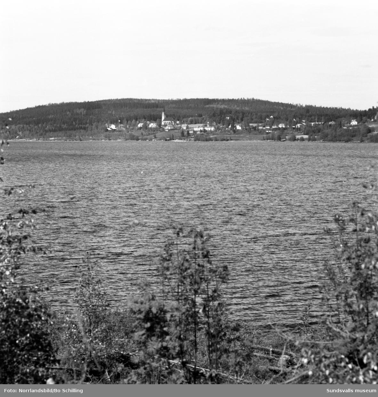 Holm och kyrkan fotograferat från andra sidan sjön.