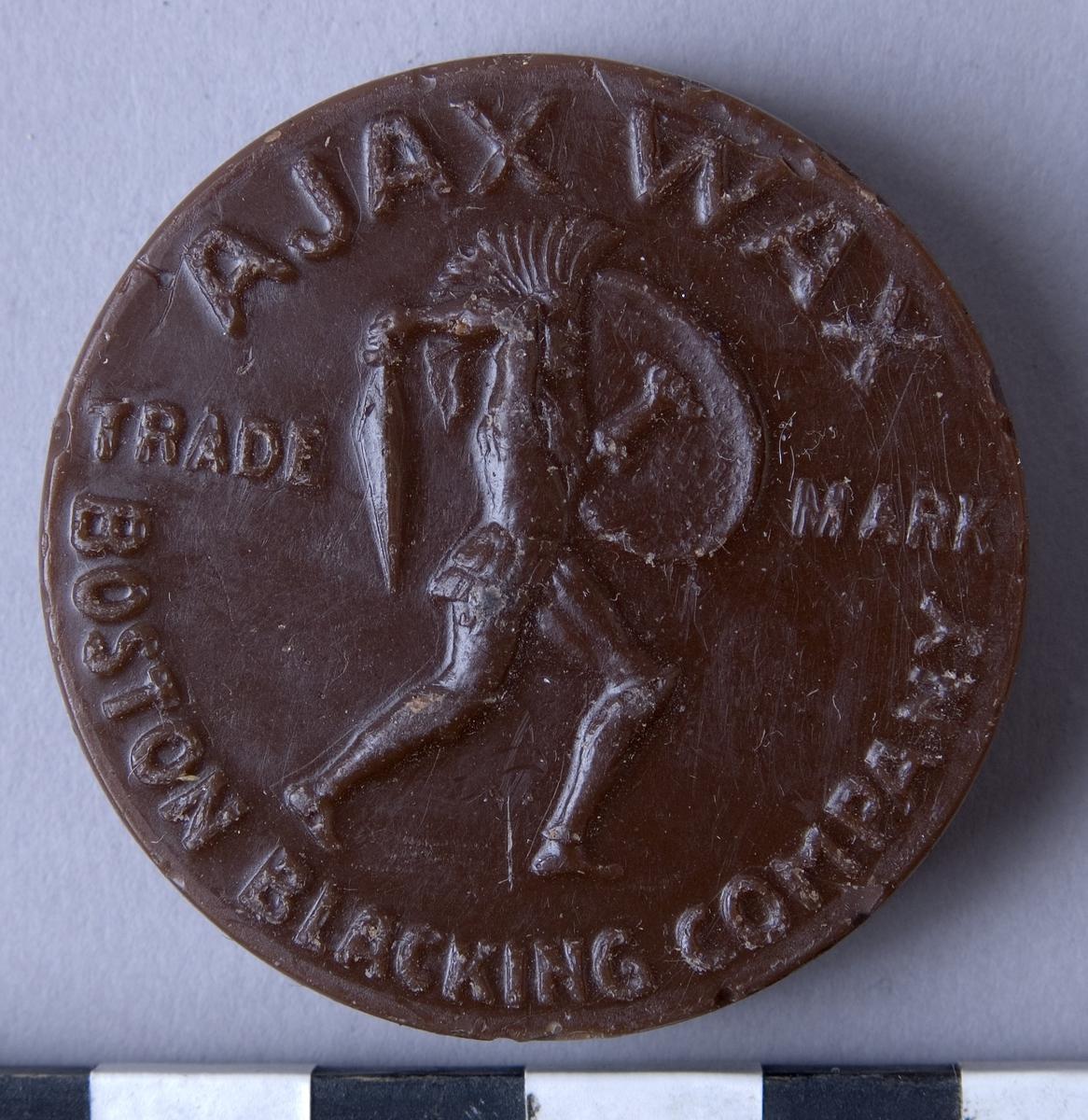 """Färgvax , fyra stycken, runda kakor  av vax i olika kulörer och fabrikat.  A: Brun, """"AJAX WAX"""" """"BOSTON BLACKING CO"""" B: Brun, """"AJAX WAX"""" """"BOSTON BLACKING CO"""" C: Svart, """"HERKULES WACHS"""" """"SCHUTZMARKE"""" D: Beige, """"AJAX WAX"""" """"BOSTON BLACKING CO"""""""