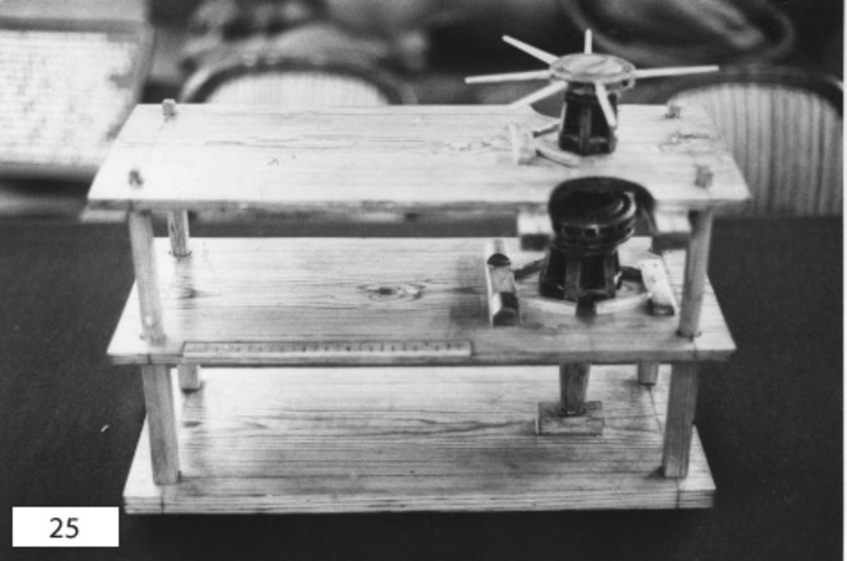 Gångspel, dubbelt, modell av trä, fernissad, med belag av metall. Tillbehör: 6 stycken spelbommar. Spelen är placerade på övre och mellersta däcken av ett tredäckat plan.