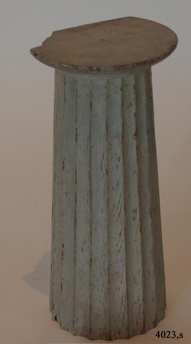 Pelare, eller kolonner, släta och räfflade (7 st halvkolonner, räfflade). 20 st. modeller av trä, avsedda som fasadprydnader. Pelarna är räfflade med halvcirkelformig basyta. De är vitmålade. Kapitälen är av närmast dorisk stil. Pelarna utgör modeller till gavelkonstruktion för nya inventariekammaren på varvet 1785-87. De sammanhängs troligen med en serie av gavelmodeller och pelare, som finns i kistan i sal 1 och vid norra delen av väggen i samma sal. (K 2244)  3/4 Kolonn, kannelerad, med kapitäl,målad i gråvitt.  H = 224mm  Bas D = 90mm  Kapitäl D = 110mm