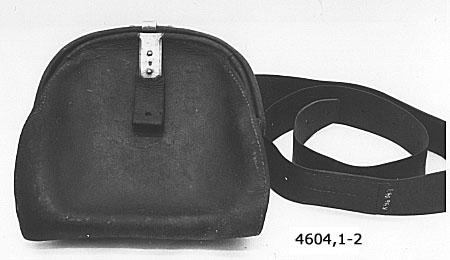 Tändrörsväska större, med livrem av svart läder. Spänne och sölja av mässing och märkta med kronstämpel. Väskan har tillhört remingtongevär M/1867-1889.