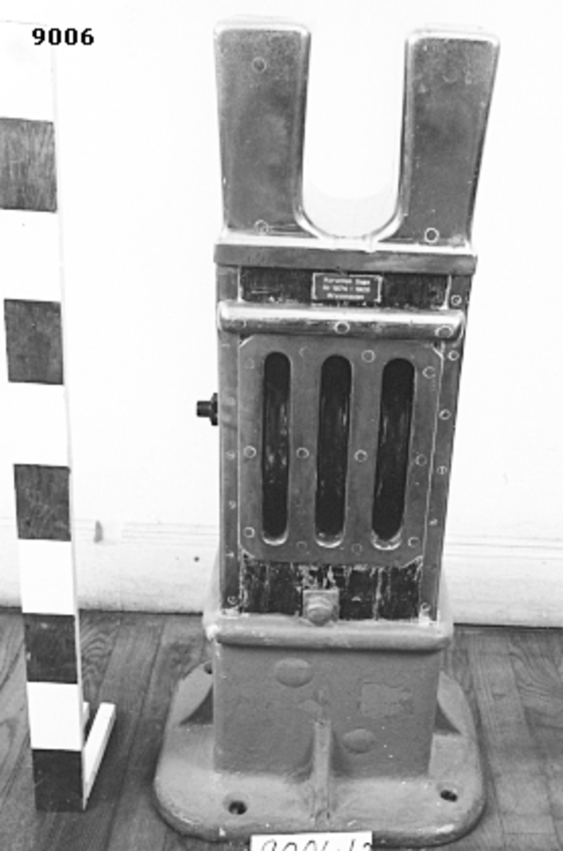 Knekt av trä mässing och gjutjärn. Rektangulär med beslag av mässing. Fastsatt i lampa av gjutjärn. På mitten försedd med tre blockskivor av gjutjärn för löpande tågvirke. Överkanten utformad till två pollare för fastgöring av tågvirket. Lampan försedd med fyra bulthål för fastsättning i däck. Märkning på bricka av mässing: Korvetten Saga År 1874-1928 Kryssmasten.