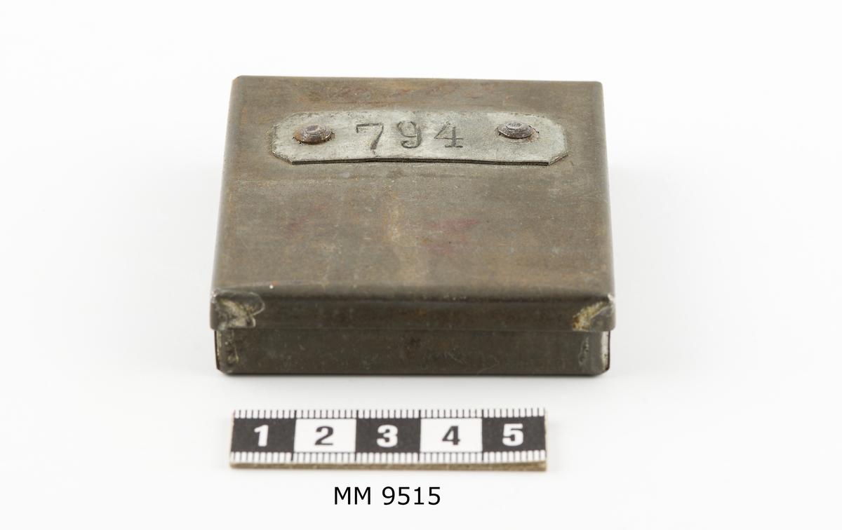 Ask, avlönings-, av bleckplåt. rektangulär. Asken är in- och utvändigt stämplad med arbetarens nummer, 794, på plåtar av bleck, fastnitade invändigt i botten, utvändigt på locket.
