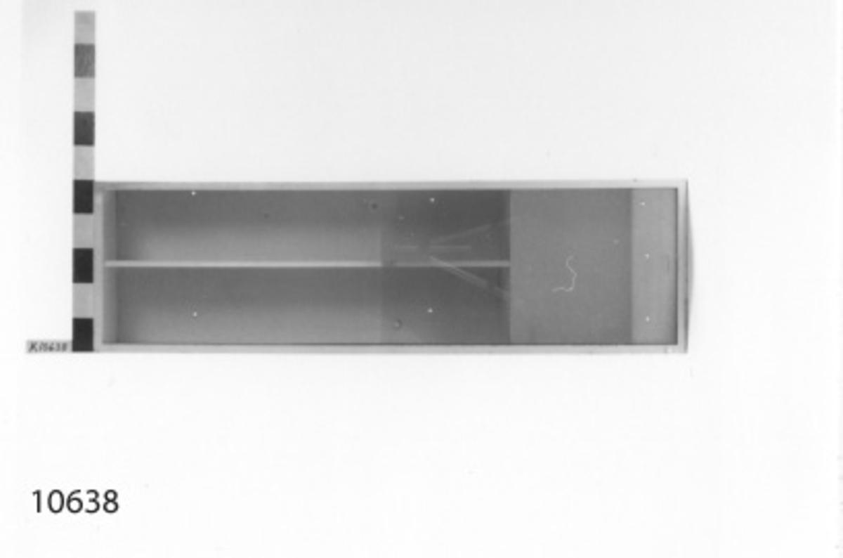 Skåp av plåt. Har två hyllor samt skjutbara glasdörrar. Vitmålat. Märkning på baksidan: Pos 11.