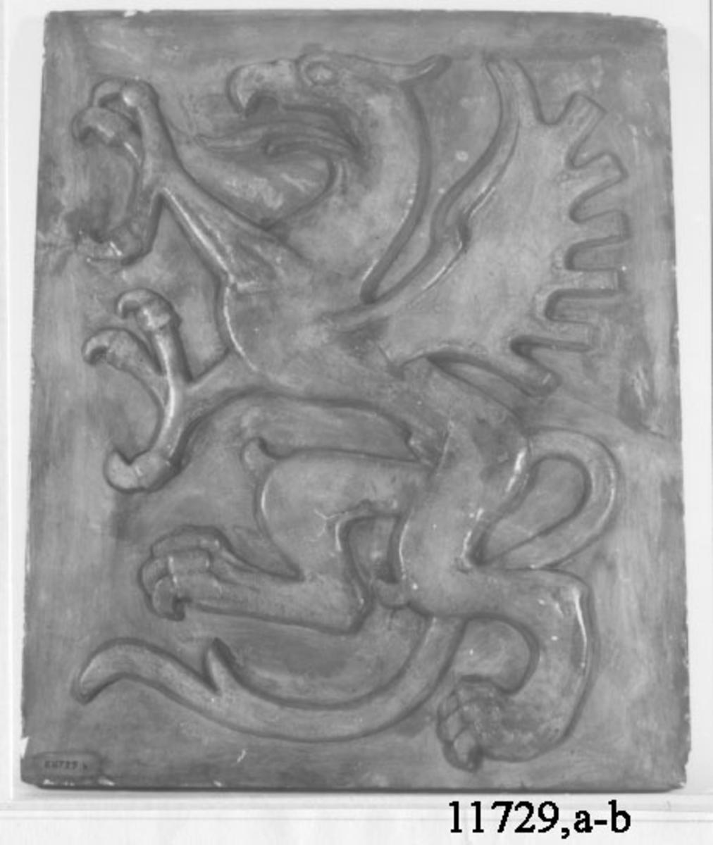 Originalmodell i gips för ubåten Gripen fartygsemblem, Utförd av skulptören Conrad Carlman, född i Karlskrona 16 januari 1891. Reliefen föreställer en grip, stående på bakbenen, färdig till anfall. A: emblem för styrbordssidan. B: emblem för babordssidan.