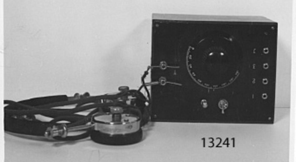 Består av en brunbetsad trälåda med överdel av bakelit. På dess undersida, reglerbar spole, genom vilken svängningskretseni antenn bildas, kondensator, kopplad mellan hörtelefonens poler (verkar som förstärkare). På översidan ratt för inställning av spolen, kopplingsskruvar för hörtelefon, fyra jack, tre för antennanslutning och en för jordanslutning. Detektorn (ej komplett, den saknade delen ersatt med en annan) verkar som likriktare, dess uppgift är att göra intermittent eller modulerad högfrekvenssignal uppfattningsbar. Till apparaten hör hjälmtelefon, märkt: DE NESPER PHONE 2000.