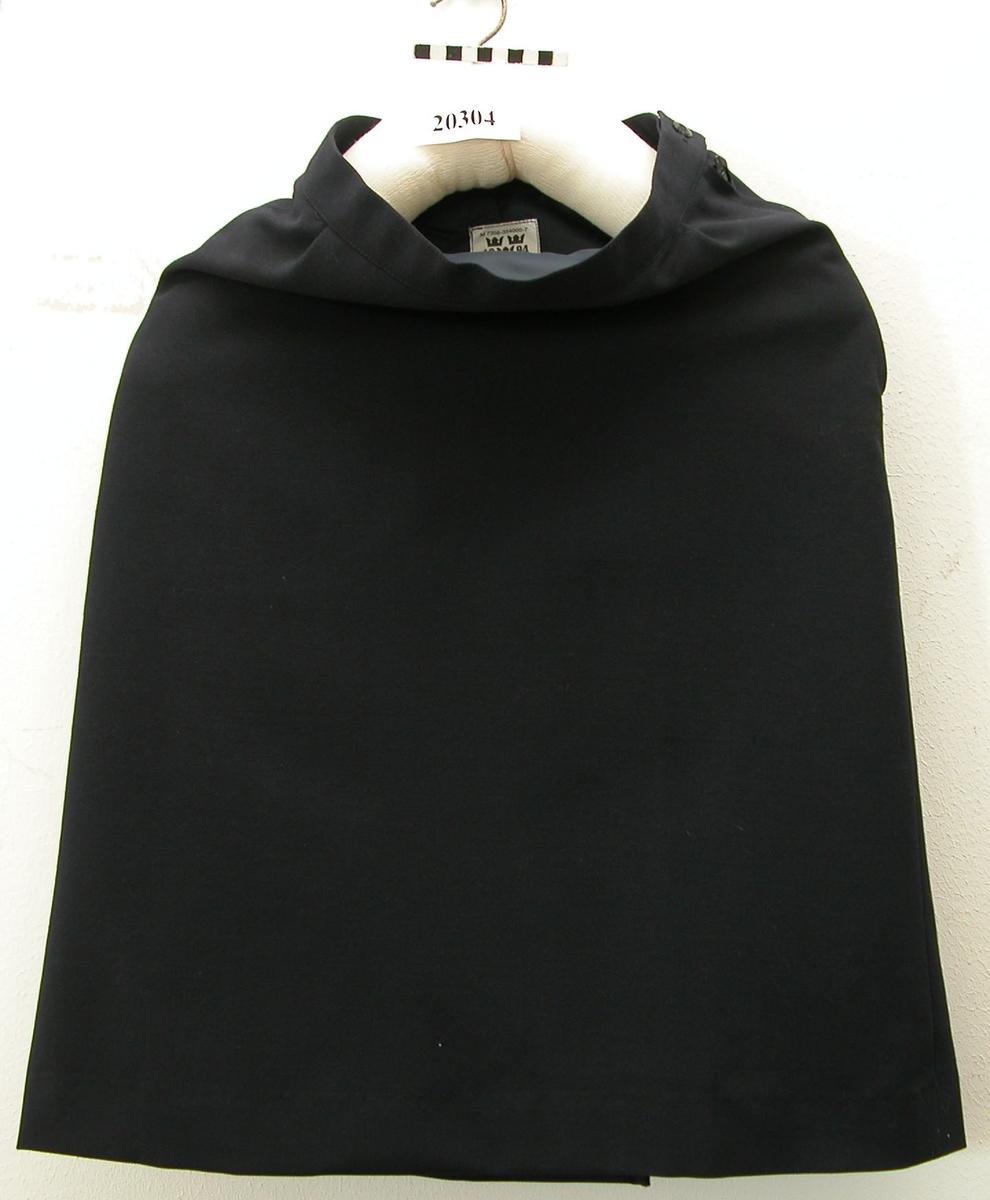 Kjol av mörkblått tyg, 65% polyester, 35% ull. Utställd modell, försedd med flatveck i bakvåder. Förlängt midjeband som knäpps i vänster sidsöm. Linning utan hällor. Fodrad med blått tyg. Lapp med materielnummer: M 7356-354000-7.
