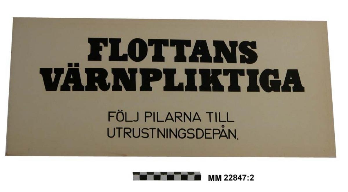 Skylt. Text i svarta bokstäver på vit botten: FLOTTANS VÄRNPLIKTIGA FÖLJ PILARNA TILL UTRUSTNINGSDEPÅN.  Papp 3 mm.