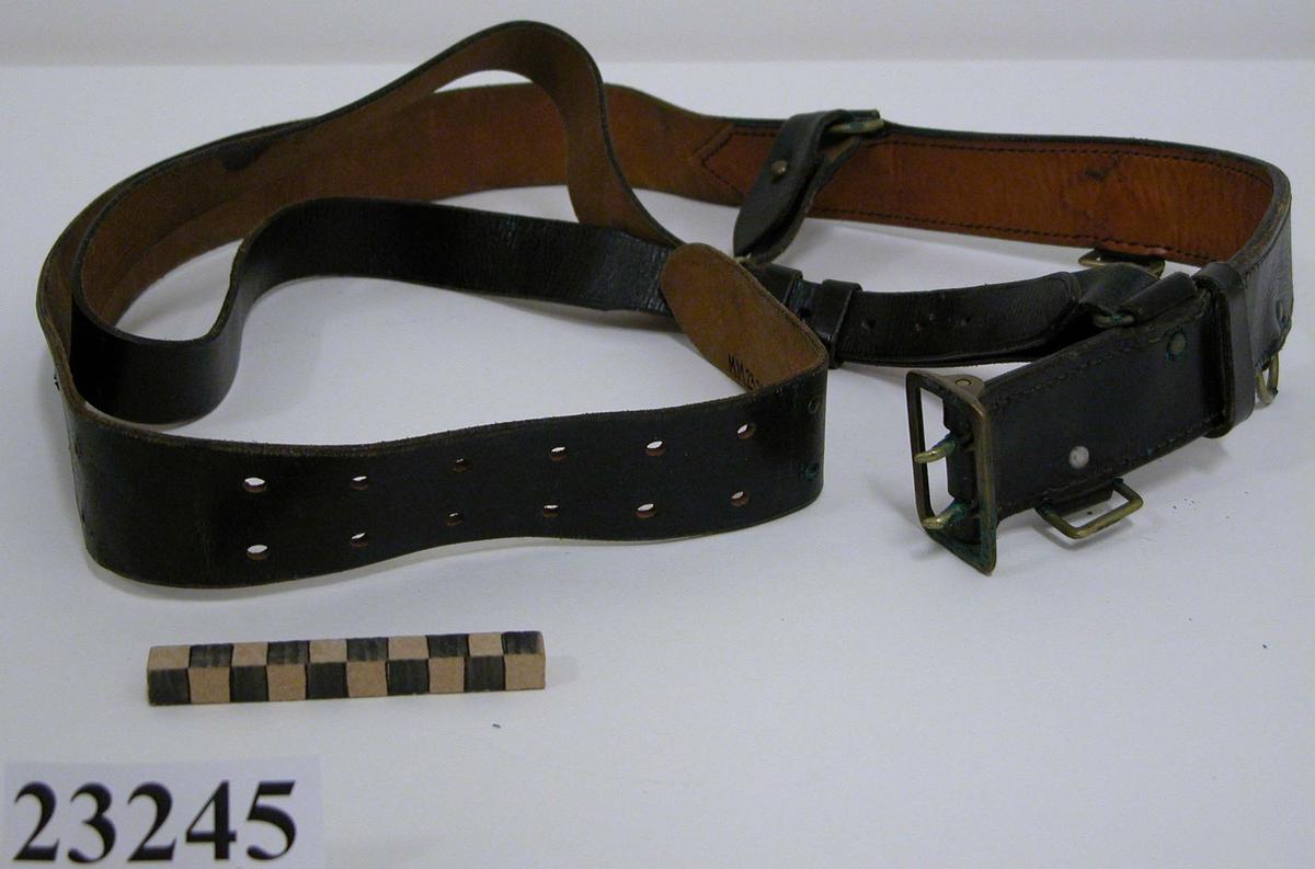 Koppel av svart läder, med söljor, hakar och spänne av mässing. Till livremmen är fäst en justerbar axelrem. Livremmen är stämplad på insidan: tre kronor och 130.
