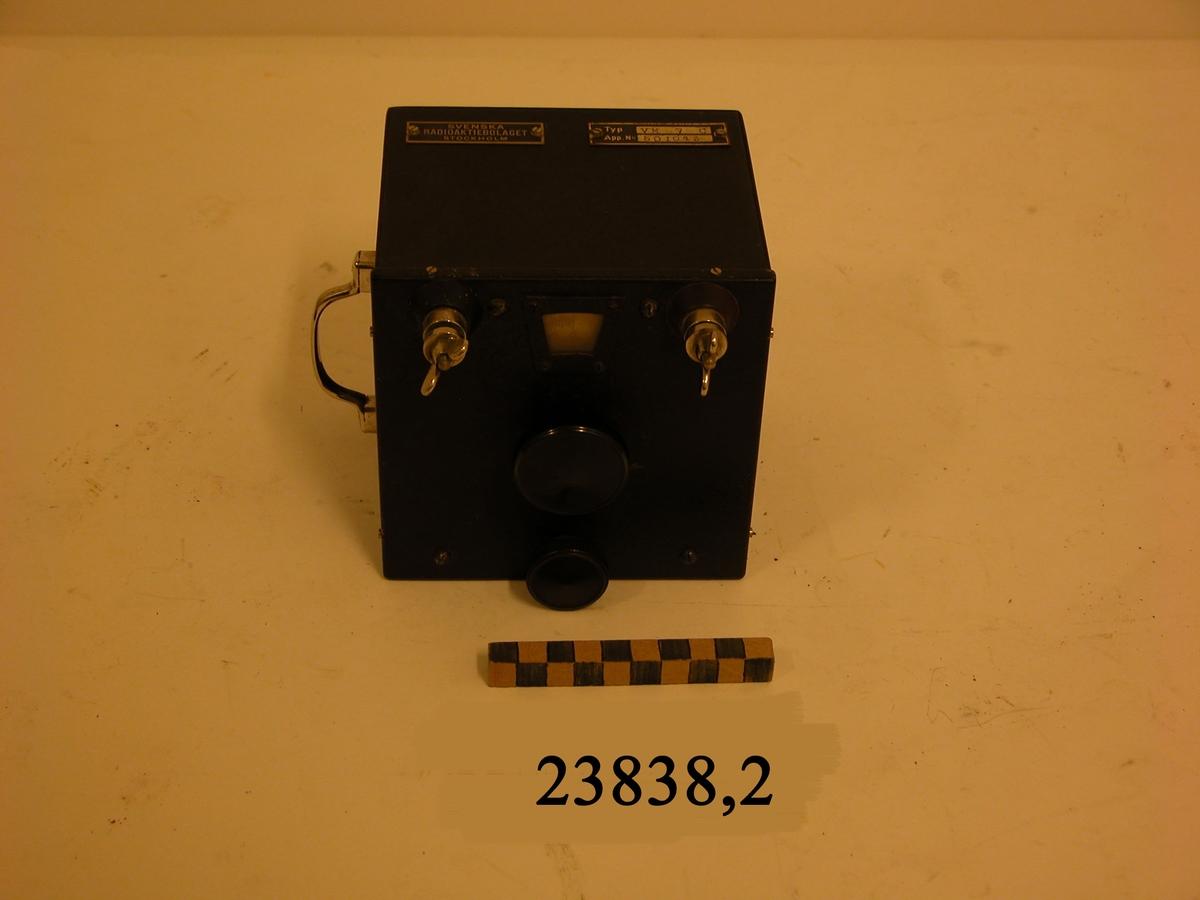 Svart rektangulär låda av metall. På framsidan två skruvar med vingmuttrar. Mellan dessa ett litet fönster med inställbar graderad skiva. Därunder två rattar av svart plast. På lådans översida två fastskruvade metallbleck med text: SVENSKA RADIOAKTIEBOLAGET STOCKHOLM samt Typ VM 7 C App No 501043. På en av lådans sidor ett bärhandtag av metall.
