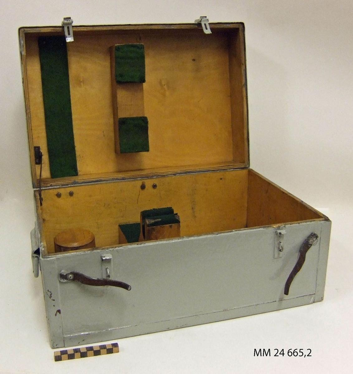 """Låda av trä till målangivningskikare. Rektangulär, gråmålad låda med lock. Handtag av metall på sidorna. Spännen av metall samt läderrem som dras igenom spännet som låsning. Grön filtmatta inuti som skydd för kikaren. I lådan två runda stöd som troligen används till extrautrustning. Märkning med tusch i locket  """"12""""."""