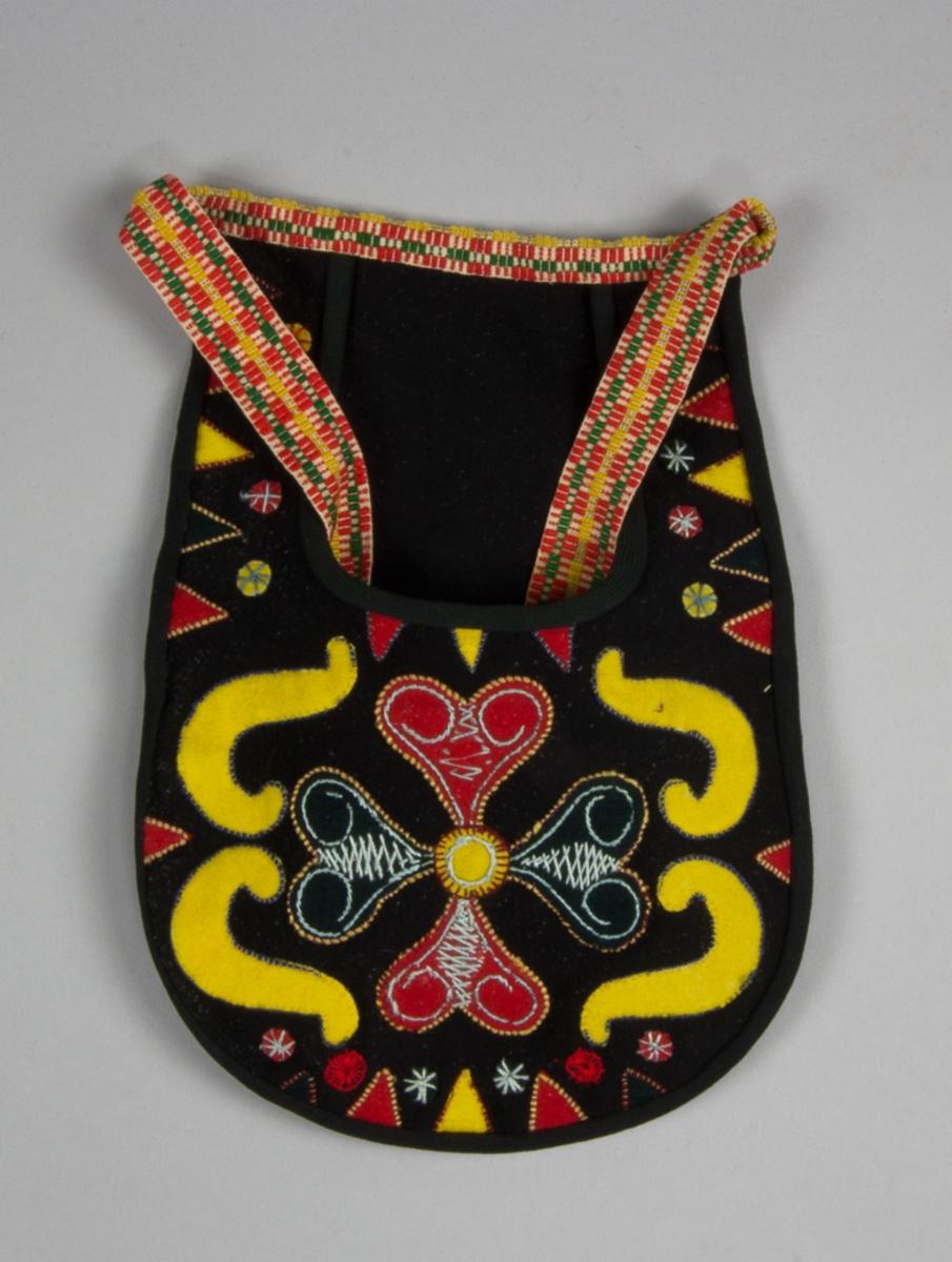 Kjolsäck till dräkt för kvinna från Leksands socken, Dalarna. Modell med u-formad öppning. Tillverkad av svart ylletyg, kläde, med applikationer av kläde i rött, gult och svart, fastsydda med läggsöm i olika färger. Centralt placerad hjärtblomma med slingor på sidorna och trekanter vid kanterna, dessutom ett antal små rundlar. Broderier utfört med bomullsgarn i ljusblått, rött och gult, förutom läggsöm även flätsöm, stjälksöm, langettsöm och sticksöm. Framstycket fodrat med svart bomullstyg, fabriksvävt, kypert. Kantad runtom med svart diagonalvävt band. Bakstycke av svart kläde. Midjeband handvävt med plockat mönster i rött, gult och grönt på vit botten. Små tofsar av rött, gult och mörkgrönt ullgarn i var ände.