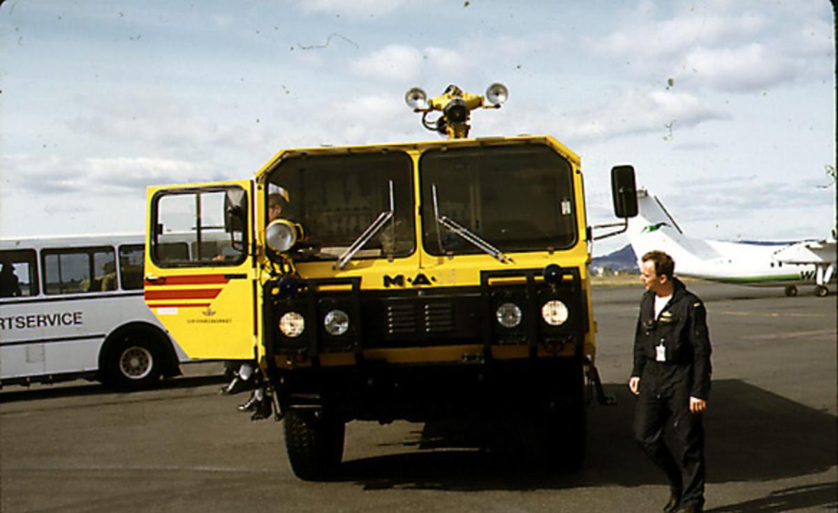 Lufthavn, Diverse aktiviteter. Branntjenesten, person ved siden av kjøretøy. Byss og fly i bakgrunnen.