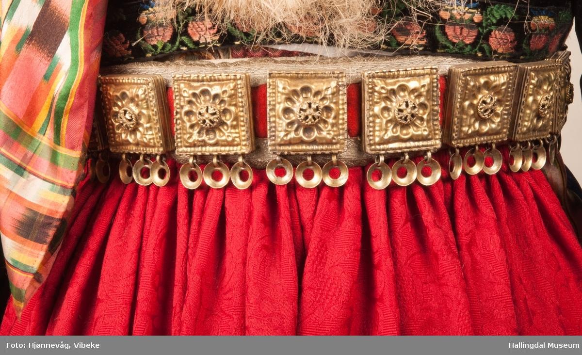 Drakten står utstilt i den faste bunadutstillingen på Hallingdal Museum, Nesbyen.  Den ble satt opp på grunnlag av et bilde fra Norsk Folkemuseum, tatt ang. av Axel Lindahl.  Tidfestet til 1877-78.  Høyde på overdel ble bestemt etter lengden på trøya.  Utelatelsen av det store bryststykket og andre forandringer ble diskutert med Ågot Noss og godkjent.  Ny dokke ble bygd opp med utgangspunkt i stakkens mål. HFN 03387-stakk med liv.  Stakk og liv ble skilt 5.1.1999, rød ulltråd med tråklesting festet delene sammen, fjernet.  Stakk festet til liv i ny høyde med store attersting med rødt bomullsgarn.  Det ble sydd understakk i ubleket lerret med vattering av dacronvatt, for å få riktig profil. HFN 03386 Forkle er noe for kort. HFN ? Skjortering, sydd fast i skjorta. HFN 00677 sølje, sydd fast i skjorta. HFN 00533 sølje sydd fast i skjorta. HFN ? Perleklut, sydd fast i skjorta. HFN 00560 Angus Dei, påsatt ny silkesnor. HFN 06695 Silketørkle, blått, festet i forklesnora HFN 03499 Silketørkle festet i forklesnora HFN 06694 Silketørkle, rødt rundt halsen HFN 03603 Brudelue HFN 03137 Stølebelte, påsatt bendelbånd, disse ligger over skuldrene for å holde beltet oppe. HFN 03318 Linskjorte.  Vasket: desember 2000 HFN 01815 trøye i svart speilfløyel.