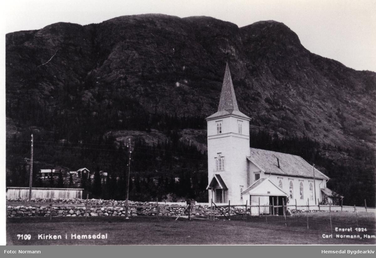 Hemsedal kyrkje med port og hestestallar. Biletet er teke i 1924. Garden Haugen i bakgrunnen