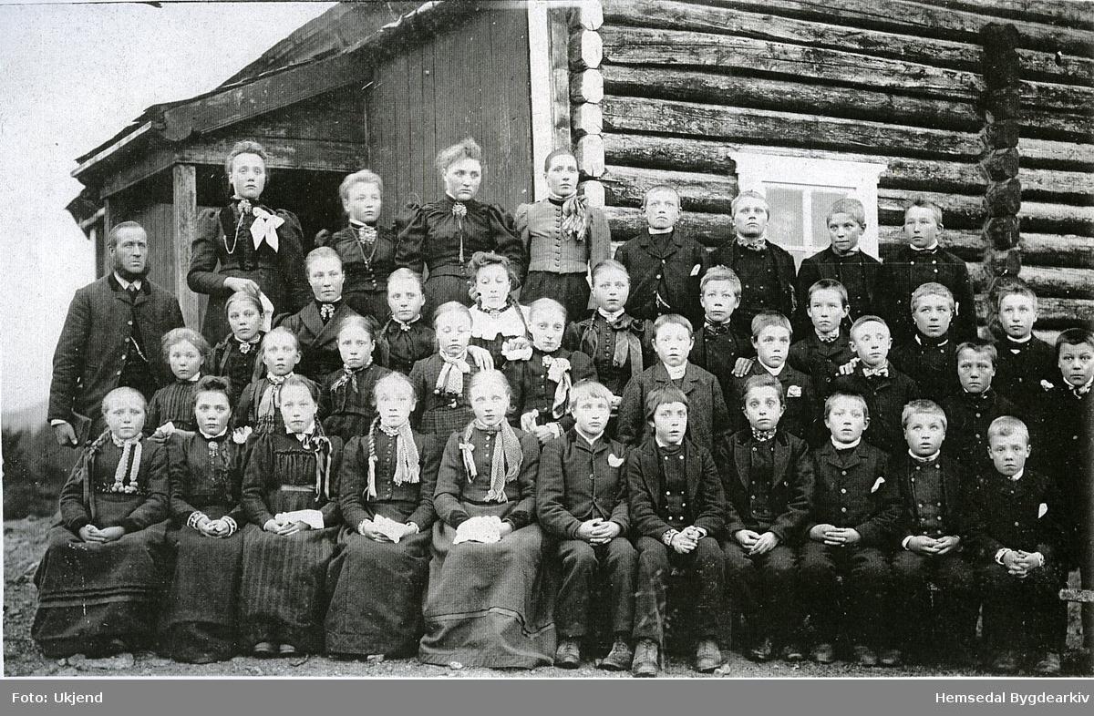"Gamle skulen på Sanden i Trøym. Huset stod ""på Sande"" i sentrum ovanfor riksvegen eller ""lina"" som dei sa i den tida.   Namneliste på personane finst i Hemsedal Bygdaarkiv."