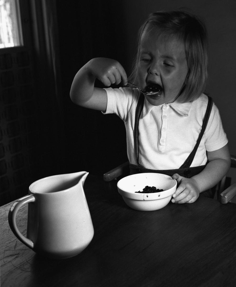 Servus bestick Flicka äter bär med sked. C.-H. Stålhanes servis från Rörstrand och Servus bestick av Sigurd Persson från Kooperativa Förbundet